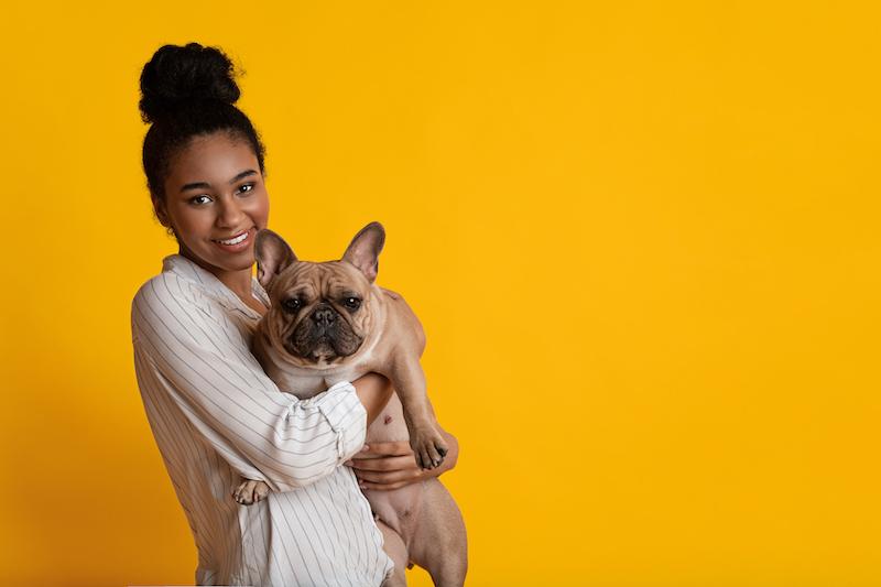 young afro woman hugging french bulldog